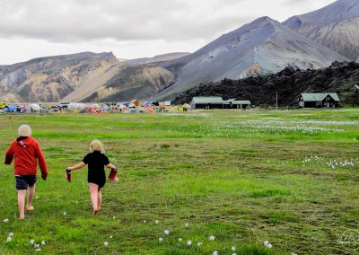 Two children walking in the grass barefeet in mountain landscape
