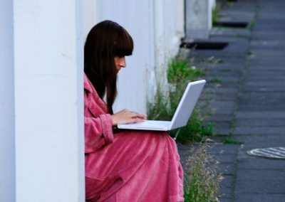Girl in a pink jacket, working on her laptop, sitting on stairs in the street