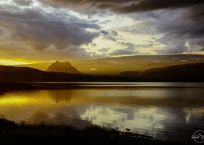 Sunset in a mountain landscape fully reflected in a lake