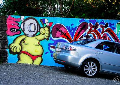 Car parked next to a wall with grafiti