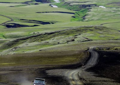 A jeep driving on a mudd road across iceland