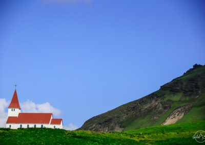 White church with red roof in a green field
