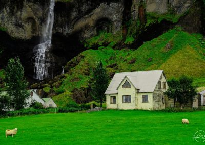 White house next to a cliff and a waterfall with very green garden