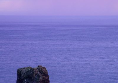 A rock in the sea during a purple sunset