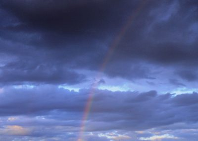 A rainbow during sunset with a stormy sky, above a cliff