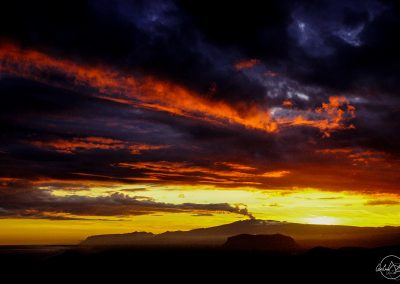 Silhouette of a volcano and its smoke melting in the black and red clouds at sunset
