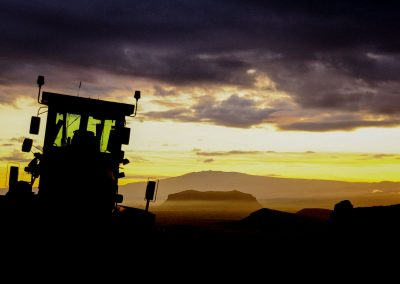 Silhouette of a tractor lost among mountains at sunset