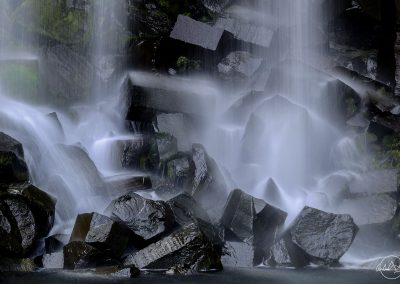Close up of the end of a waterfall on black stones