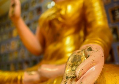 Bottom view of a tall golden buddha statue, with the hand facing the camera and the rest blurry in the background