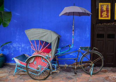 Old tuk tuk with an umbrella in font of a blue wall