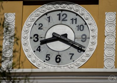 Large clock owith the figures in anti-clockwise order, put on a yellow facade