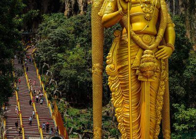 Huge golden buddha statue in front of stairs at the entrance of a cave