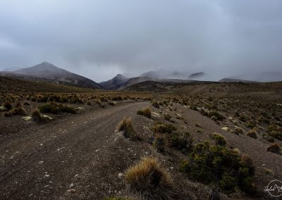 Black trail in a stormy and grey sky, heading towards hills