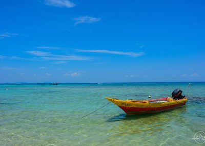 Turquoise sea with a yellow and red wooden boat