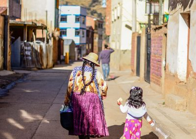 A mother and her daughter walking in a street both wearing pink skirts