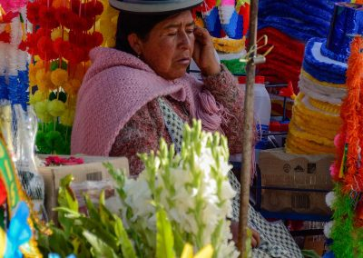 Woman with a tall black hat, sitting in a street market surrounded by colorful paper necklaces and hats