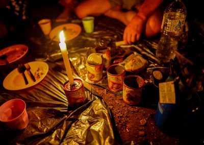 Plastic plates and candle on a tin can, on the ground in a cave