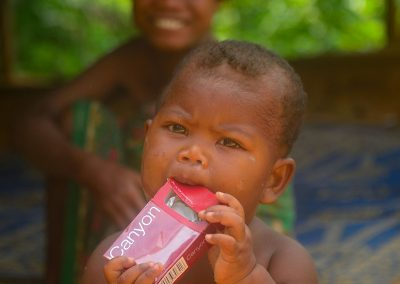 Young child chewing an empty box of cigarettes