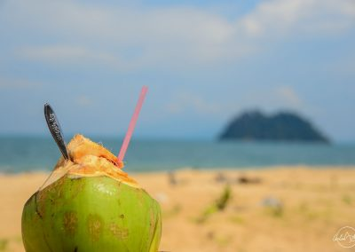 Coconut with a straw and a spoon facing the beach, sea and a far away island