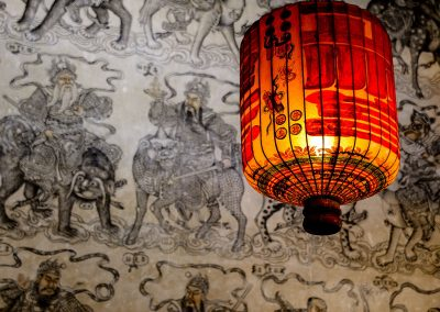 Red lantern lit with black paintings of chinese dragons in the background
