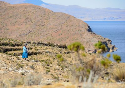 Lady in blue, in the middle of a rocky landscape, facing the blue sea