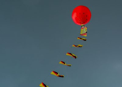 Red balloon with a line of yellow and red flags, floating in a dark grey sky