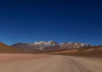 Road of red sand in the middle of red mountains with top covered by snow