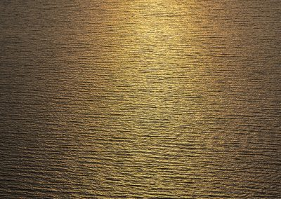 Reflect of a golden sunset in the sea forming thin lines