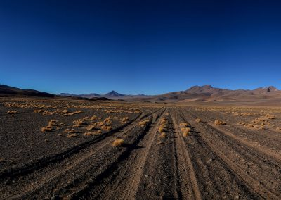 Tire marks in the black sand of the desert towards far away mountains