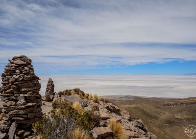 On top of a hill with rock sculptures, facing the white salt salar