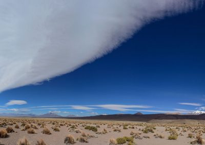 Panoramic view of long plain with a huge and extremely long white cloud in the sky