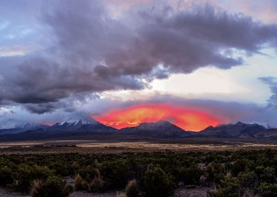 Chain of mountains at dusk, above them, a part of the sky is red, as if a fire was burning