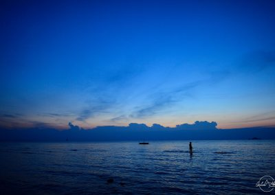 Dark blue sky and water with a silhouette of a lady standing in the water