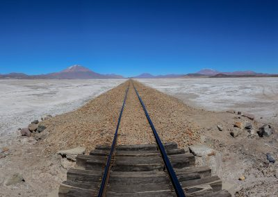 Train rails in the midlde of the desert with mountains on each side