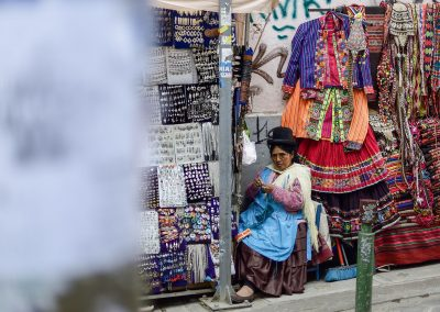 A woman with a tall black hat knits in the street of La Paz, between a stall of jewels and a stall of colorful clothes