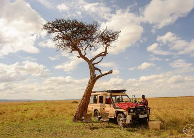 Safari jeep beneath a tree in the savannah with dining table ready for breakfast