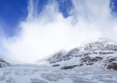 Panorama view on a glacier, covered in snow and surrounded by mountains