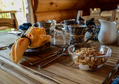 Bowl of granola on a wooden table next to blue and white dishware