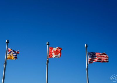 Three flags flying in the blue sky