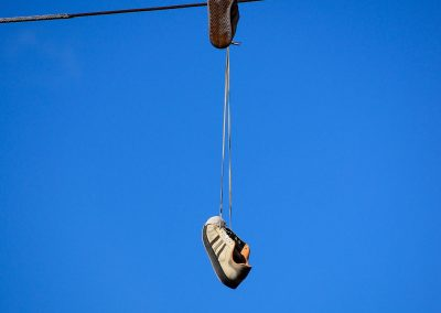 A pair of shoes hanging on wires with blue sky