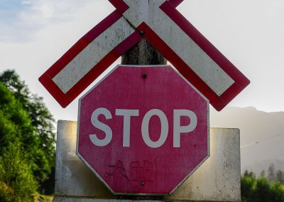 Stop sign and a cross in front of rails
