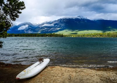 White surfboard facing a lake