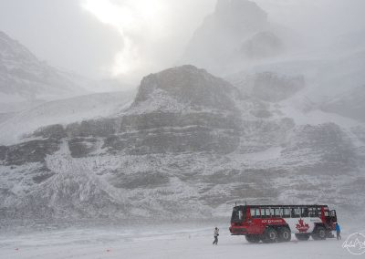 Red bus on a glacier, with a mountain in the background and in the snow
