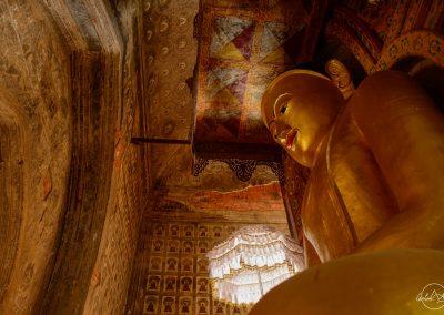 Tall Buddha golden statue from below inside a golden temple in Myanmar