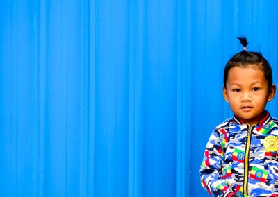 Little Burmese child in front of a blue wall