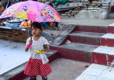 Little girl walks down stairs of a temple in Myanmar with a Disney princesses umbrella