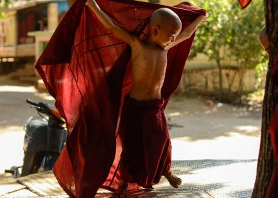 Child monk running and laughing in a garden in Bagan