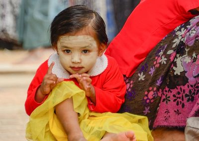 Young burmese child sitting in a temple in Bagan with thanaka paste on her face