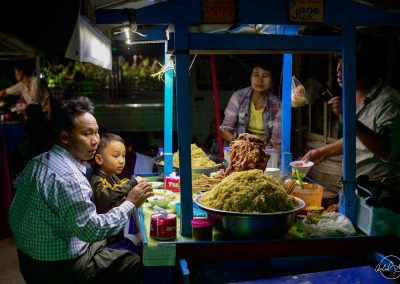 A dad and his son sitting at a food stall in a market at night
