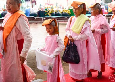 Female monks queuing for offering in Ananda temple with a young girl looking at the camera